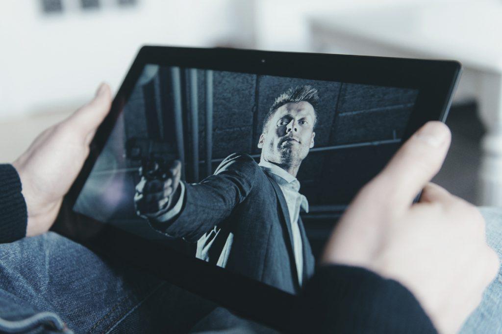 Iemand kijkt op vakantie tv op zijn tablet